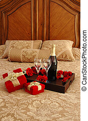 Surprise - Gifts, champagne, and roses on a bed