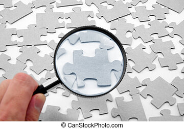 puzzle and magnifier, business concept