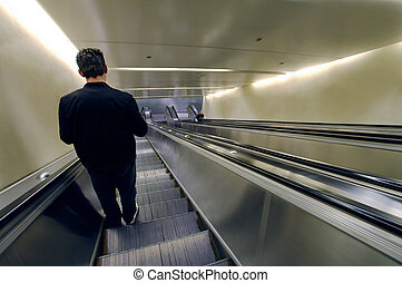 going down - solitary man going down using an escalator