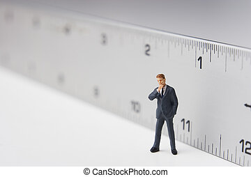 Measure of a man - Business figure placed next to a ruler