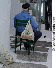 Greek Man - Man sitting in chair in Mykonos,Greece