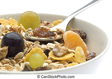 muesli with grapes and spoon in bowl close up