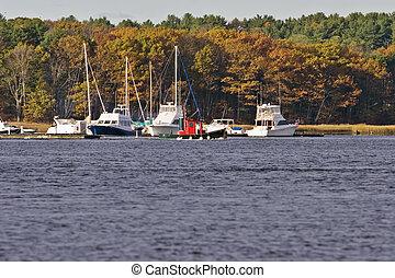 Tug Boat - Small red tug boat moving sailboats into marina