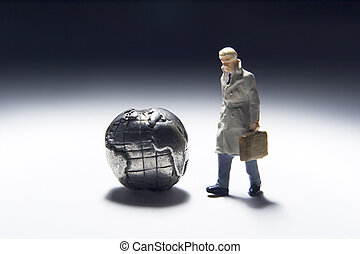Global biz travel - Business figurines and earth globe.