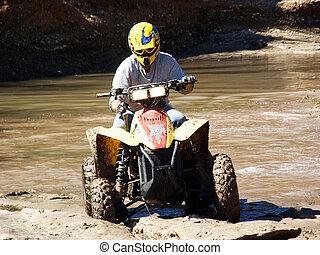 ATV Muddy Trails - A shot of a young man running some muddy...