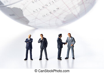 Global business team - Business figurines and earth globe.