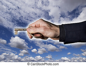 key to the future - Hand holding antique Key against a dark,...