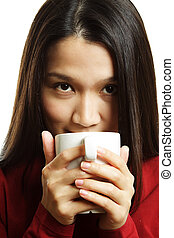 Drinking coffee - A beautiful young woman drinking a hot cup...