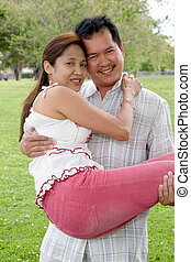 Loving couple - Man carrying his girlfriend in the park