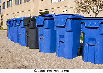 Garbage bins - Row of blue garbage bins with one black bin...