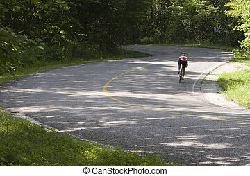 Cyclist on curve - Cyclist negotiating a twisty country...