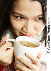 Drinking - A beautiful young woman holding a cup of hot...