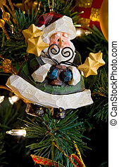 Santa Claus ornament hanging on a lighted Xmas tree