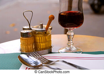 Place setting in outdoor cafe with glass of red wine