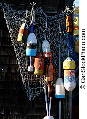 Old buoys on a netted wall at fishing shack