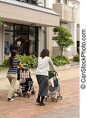Mothers - Two mothers and their children in prams