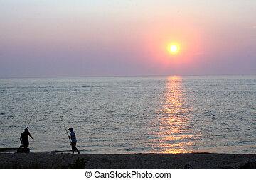 SurfFishingAtDusk 5 - Two silhouetted men surf fishing at...