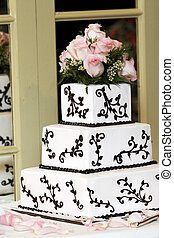 Wedding Cake - a wedding cake with pink roses sitting on a...