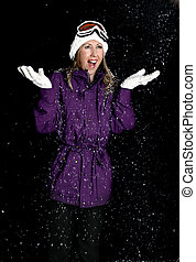 Snowy Night - A woman wearing a warm parka, beanie and...