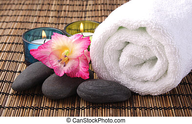 Aromatic Spa - orchid, candle pebbles and white towel on...