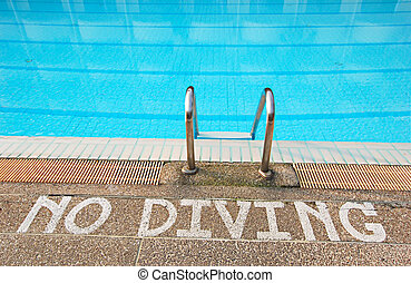 No diving sign at edge of swimming pool