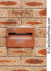 red mailbox in red brick wall, detail photo
