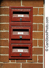 mail boxes - three red mail boxes, brown/orange brick wall