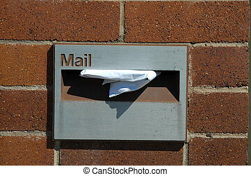 mailbox - grey maibox in a red brick wall, white paper in it