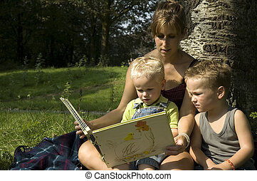 Reading a book - Family reading a book while on a summer...
