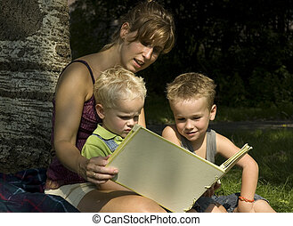 Outside learning - Family reading a book while on an outside...