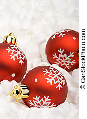 Three red Christmas balls lying on a bed of foam chips