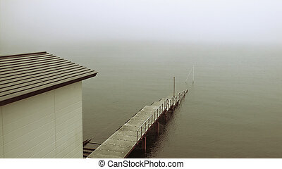 old pier in mist - old sinking pier and building on the...