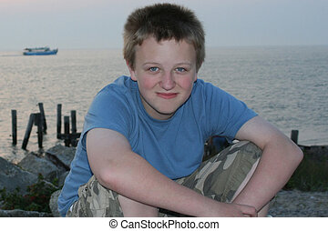 Smiling Beach Boy - Smiling teenage boy sitting on rocks by...