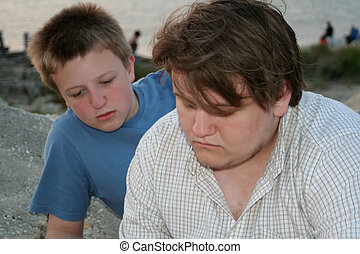 Thinking Beach Teens - Two teenage boys with thoughtful...