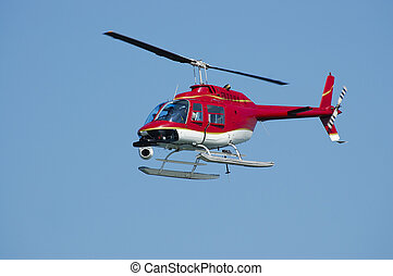 Eye in the sky - A bright red Bell 206 Jet Ranger helicopter...