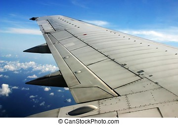 Airplane wing - An flying airplane wing in the sky with...