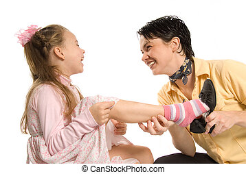 removing shoe - mom and daughter playing dress-up on white...