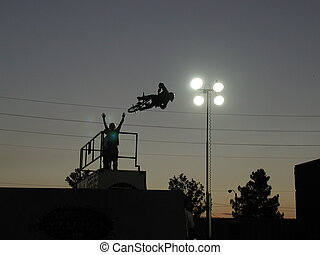 BMX Silhouette - Cheering team encourages BMX stunt rider....