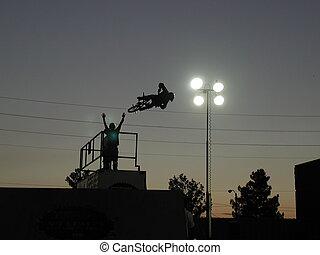 BMX Silhouette - Cheering team encourages BMX stunt rider....