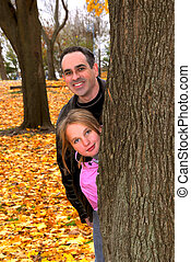Family park autumn - Father and daughter peaking from a tree...
