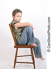sitting on chair - a child sitting on a chair for his...