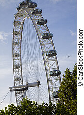 london eye - the london eye with an airplane in the...