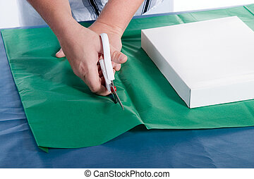 Gift Wrapping - Lady cutting wrapping paper with gift being...