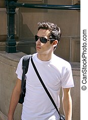young man with shades - a young man walking through the city...
