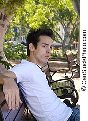young man on bench - a young man sitting on a park bench