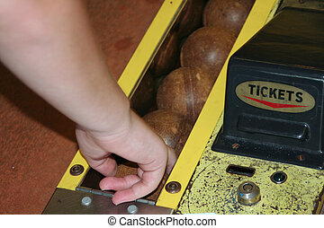 Skee Ball 3 - Teenager reaching for a ball in a skee ball...