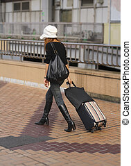 Woman travelling - Woman with travel bag walking in a city
