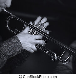 Trumpet player. Focus on the finger of the saxophone player....