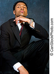 Confidence - An African-American business man sits...