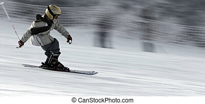 Little skier - Young boy wearing helmet speeding on the skis